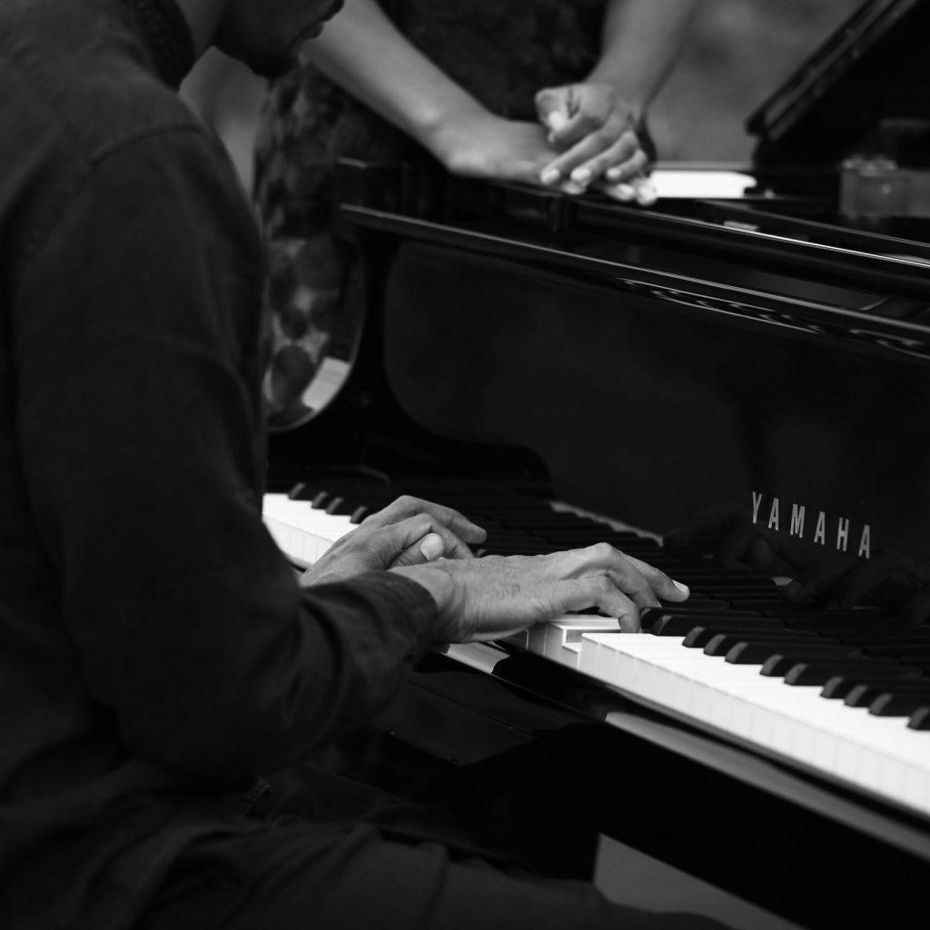 Laura Prince et Grégory Privat mains posées sur piano noir et blanc