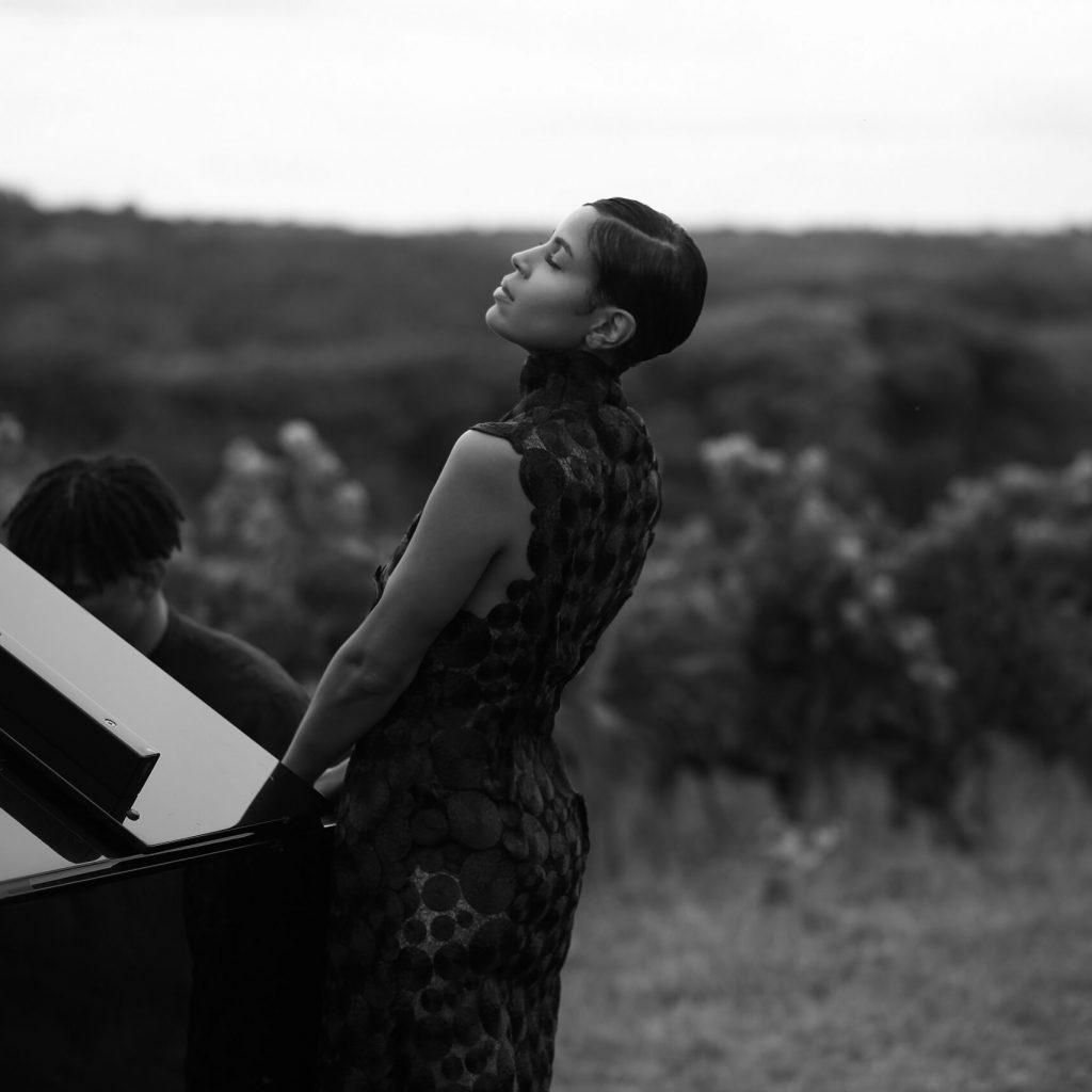 Laura Prince près du piano noir et blanc